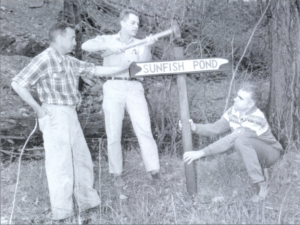 Glenn Fisher, Thomas, Ritter, and Casey Kays plant a sign to Sunfish Pond